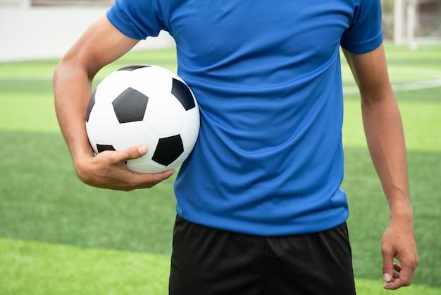 Joueur de football portant une chemise bleue, tenant un ballon de football noir.