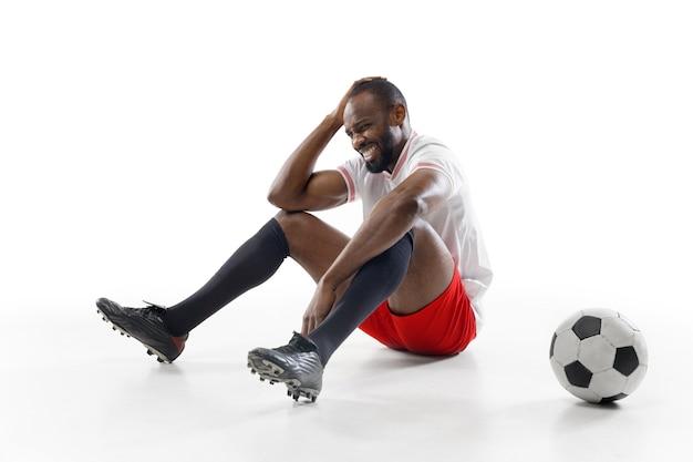 Joueur de football professionnel isolé sur le mur du studio blanc