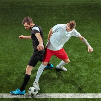 Joueur de football s'attaquant à la balle sur l'herbe verte