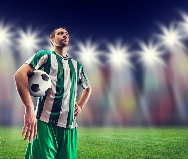 Joueur de football tenant un ballon contre la lumière