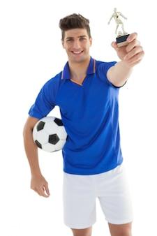 Joueur de football tenant le trophée des vainqueurs