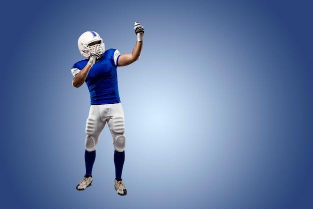 Joueur de football avec un uniforme bleu faisant un selfie sur un mur bleu