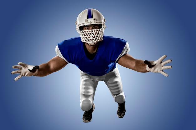 Joueur de football avec un uniforme bleu faisant un tacle sur un mur bleu