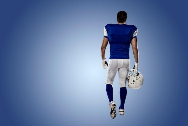 Joueur de football avec un uniforme bleu marchant, montrant son dos sur un mur bleu
