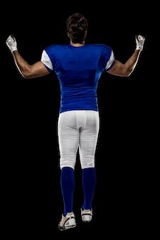 Joueur de football avec un uniforme bleu marchant, montrant son dos sur un mur noir