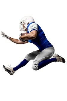 Joueur de football avec un uniforme bleu s'exécutant sur un mur blanc