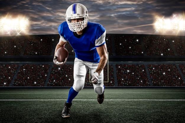 Joueur de football avec un uniforme bleu s'exécutant sur un stade