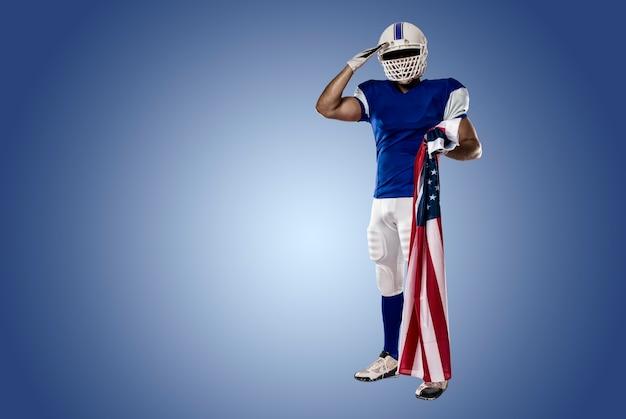 Joueur de football avec un uniforme bleu saluant avec un drapeau américain, sur un mur bleu