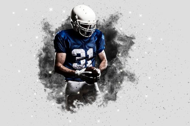 Joueur de football avec un uniforme bleu sortant d'une explosion de fumée.