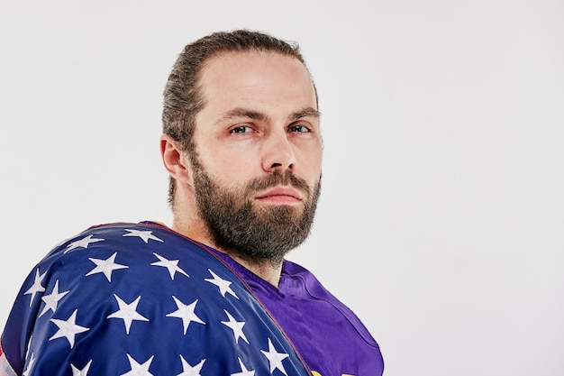 Joueur de football avec l'uniforme et un drapeau américain sur ses épaules, fier de son pays,
