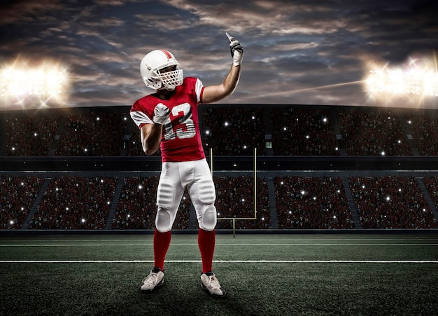 Joueur de football avec un uniforme rouge faisant un selfie sur un stade.