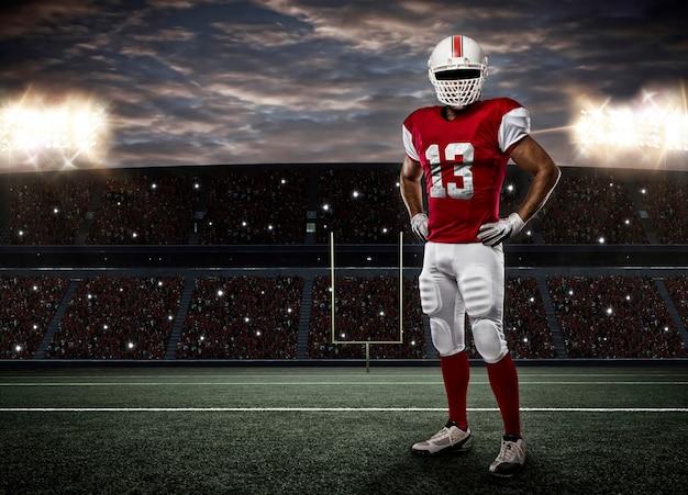 Joueur de football avec un uniforme rouge sur un stade.