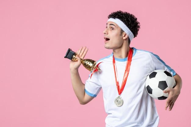 Joueur de football vue de face en vêtements de sport avec coupe d'or et médaille