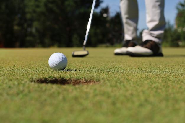 Joueur de golf au putting green frappant la balle dans un trou.