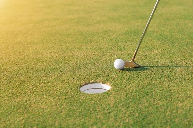 Joueur de golf au vert mettant la balle de golf dans un trou. gros plan sur la balle de golf et le putter.