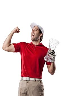 Joueur de golf dans une chemise rouge célébrant avec un trophée de verre dans ses mains, sur un espace blanc.