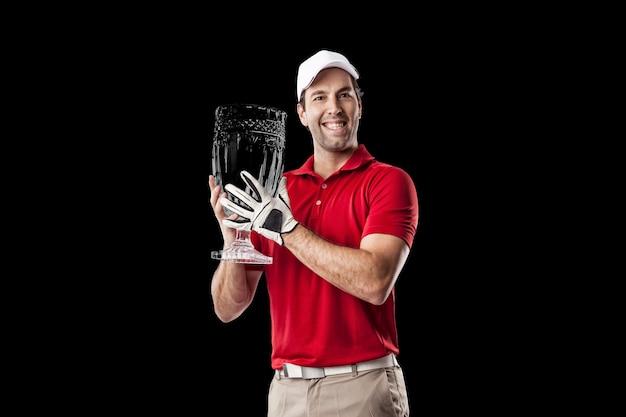 Joueur de golf dans une chemise rouge célébrant avec un trophée de verre dans ses mains, sur fond noir.