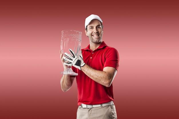 Joueur de golf dans une chemise rouge célébrant avec un trophée de verre dans ses mains, sur fond rouge.