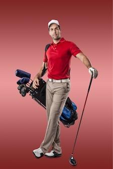 Joueur de golf dans une chemise rouge, debout avec un sac de clubs de golf sur le dos, sur fond rouge.