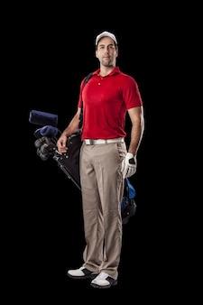 Joueur de golf dans une chemise rouge, debout avec un sac de clubs de golf sur son dos, sur fond noir.