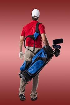 Joueur de golf dans une chemise rouge marchant avec un sac de clubs de golf sur son dos, sur fond rouge.