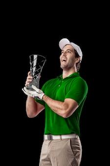 Joueur de golf dans une chemise verte célébrant avec un trophée en verre dans ses mains, sur fond noir.