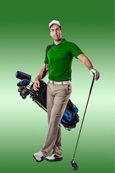Joueur de golf dans une chemise verte, debout avec un sac de clubs de golf sur son dos, sur un fond vert.