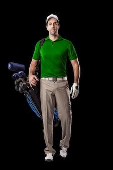 Joueur de golf dans une chemise verte marchant avec un sac de clubs de golf sur son dos, sur fond noir.