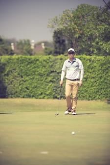 Joueur de golf sur le green frappant la balle dans un trou
