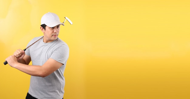 Joueur de golf homme asiatique en prenant une balançoire, isolé