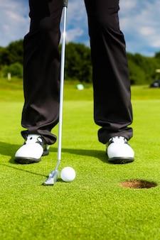 Joueur de golf mettre la balle dans le trou