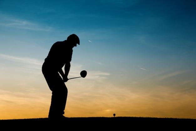 Joueur de golf senior au coucher du soleil