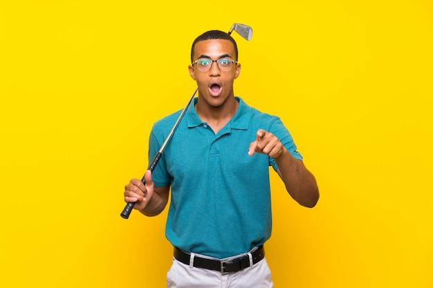 Joueur de golfeur afro-américain homme surpris et pointant devant