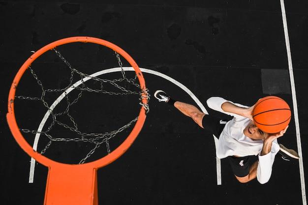Joueur de grand angle jetant le basket-ball