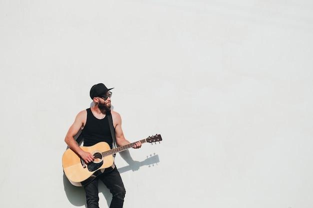 Joueur de guitare chantant à l'extérieur. joueur de guitare hipster avec barbe et vêtements noirs