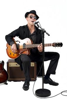Joueur de guitare chante assis sur un amplificateur