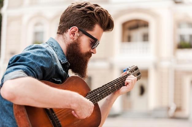 Joueur de guitare intense. jeune homme barbu jouant de la guitare alors qu'il était assis à l'extérieur