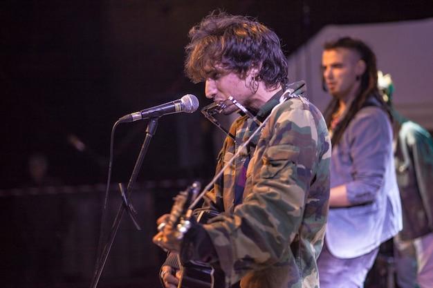 Le joueur d'harmonica de roche joue la nuit pendant un concert