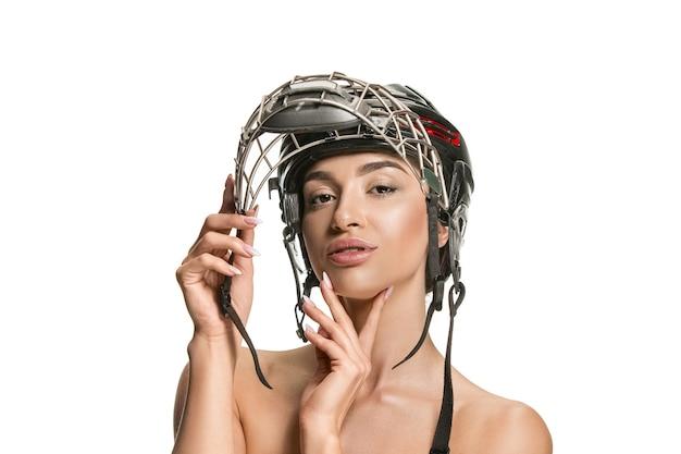 Joueur de hockey féminin se bouchent avec le casque et le masque sur le mur blanc du studio