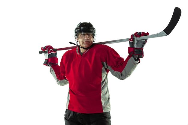 Joueur de hockey masculin avec le bâton sur un court de glace et un mur blanc