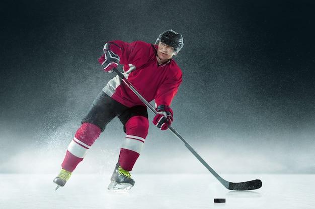 Joueur de hockey masculin avec le bâton sur un court de glace et un mur sombre