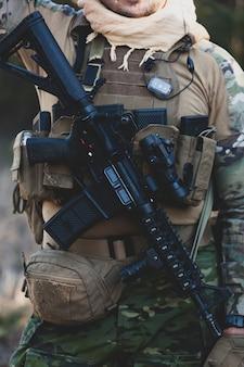 Joueur de jeu militaire airsoft en uniforme de camouflage avec fusil d'assaut armé.