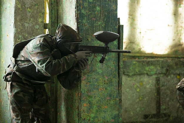 Un joueur jouant au paintball avec une arme à feu. photo de haute qualité