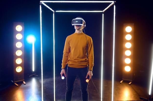 Le joueur joue au jeu en utilisant un casque de réalité virtuelle et une manette de jeu dans un cube lumineux. intérieur du club de jeu sombre, technologie 3d vr