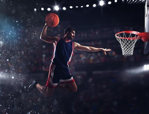 Le joueur lance le ballon dans le panier dans le stade plein de spectateurs