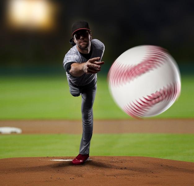 Joueur de lanceur lançant une balle, sur un stade de baseball.