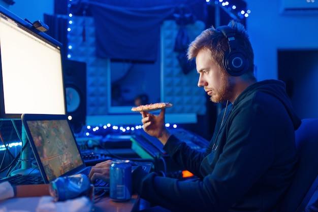 Un joueur masculin buvant une boisson énergisante sur son lieu de travail avec un ordinateur portable et un ordinateur de bureau, un mode de vie nocturne. joueur de jeux informatiques dans sa chambre avec néon, streamer