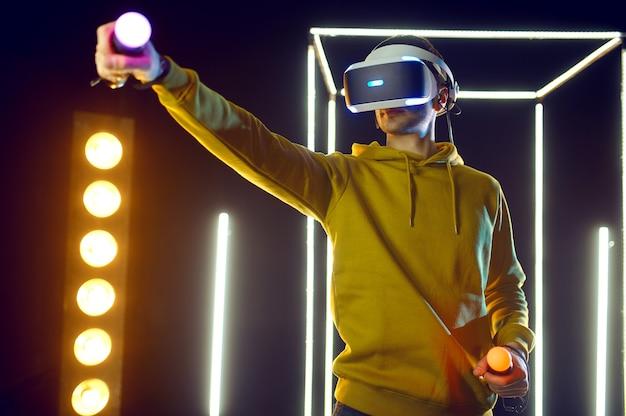 Le joueur masculin joue au jeu à l'aide d'un casque de réalité virtuelle et d'une manette de jeu dans un cube lumineux. intérieur sombre du club de jeu, projecteur sur l'arrière-plan, technologie vr, vision 3d