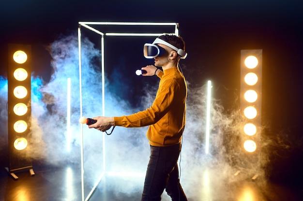 Le joueur masculin joue au jeu en utilisant un casque de réalité virtuelle et une manette de jeu dans un cube lumineux. intérieur du club de jeu sombre, technologie vr avec vision 3d