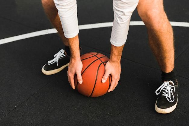 Joueur méconnaissable tenant un ballon de basket
